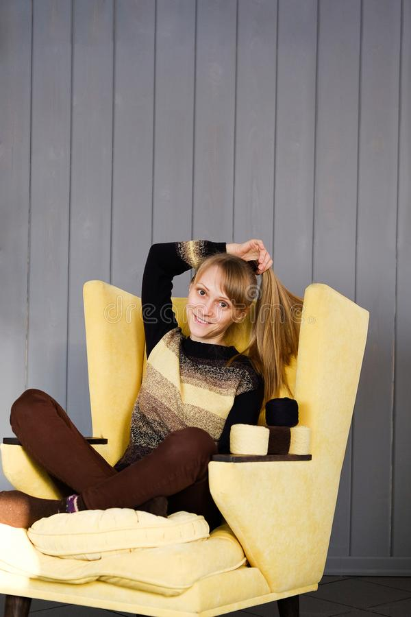 A girl in a striped knitted sweater, touching her hair, sits in a yellow chair. A young woman next to the skeins and balls of royalty free stock photography