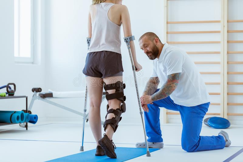 The girl after a stroke with an orthosis on a crutch leg is exercising on a blue mat in a gym in a hospital stock photography