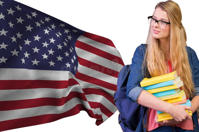 Girl student with books against american flag stock photos