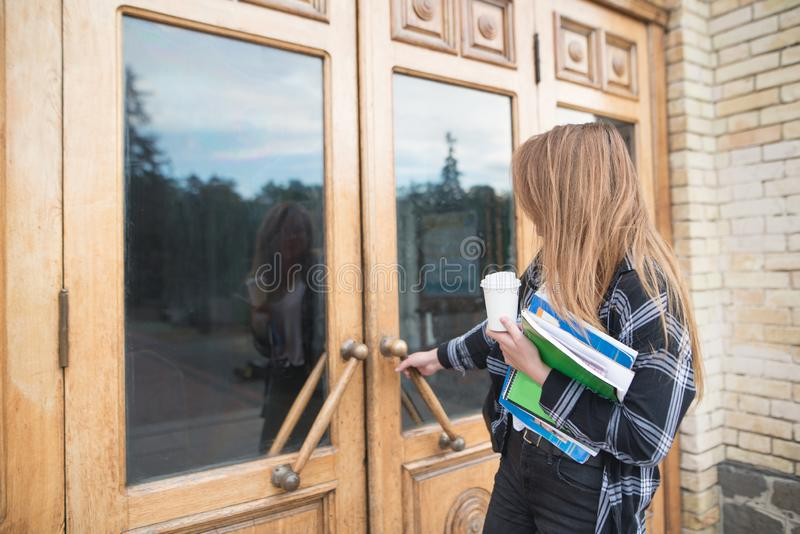 Girl student in casual clothing, books and notebooks in his hands opens the door to the university. A girl student in casual clothing, books and notebooks in his royalty free stock photography