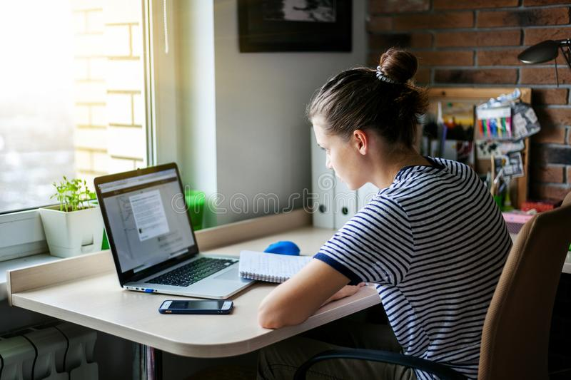 Girl student freelancer working with laptop at home by the window, education and remote work, programmer, online business stock photos