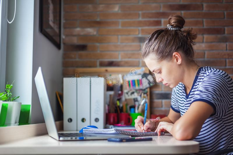 Girl student freelancer working with laptop at home by the window, education and remote work, programmer, online business stock photo