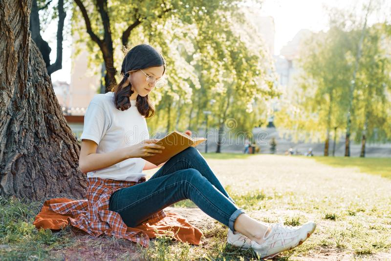 Girl student in glasses reading a book in the park sitting under a tree on the grass stock image