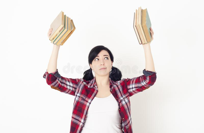 A girl student in a red plaid shirt holds stack of books at the top in each hands. Preparation for admission to. University, session or exams stock photos