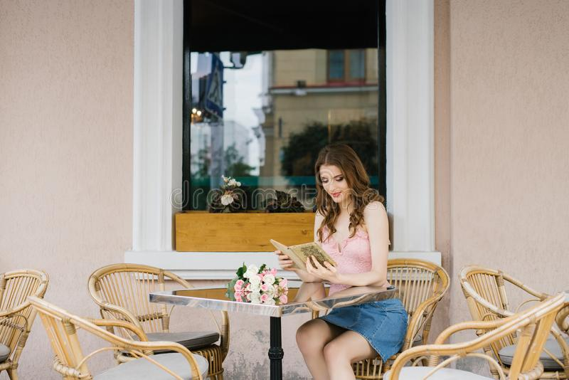 Girl student in a romantic way reading a book at a table in a street cafe. Happiness and joy. Of adolescence stock images