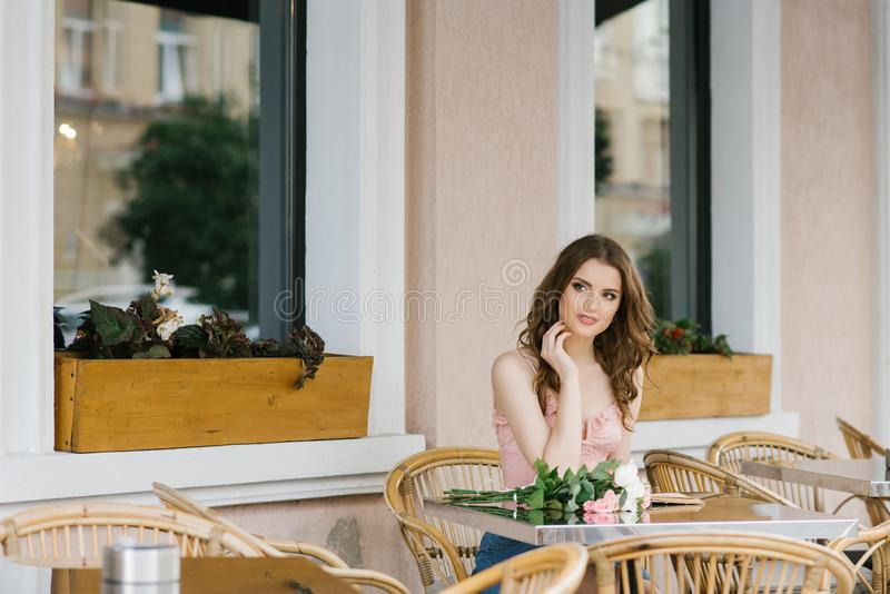 Girl student in a romantic way sitting at a table street cafe, on the table is a bouquet of roses. Waiting for the Prince in love. Guy on a date stock photos
