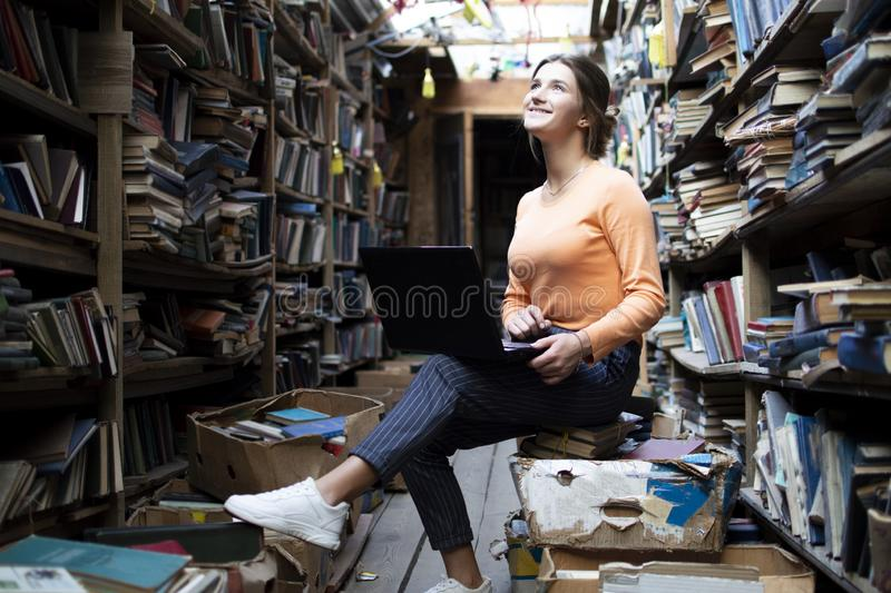 Girl student sitting in a library with a laptop and learning lessons, a woman using a computer in a bookstore, technology concept stock photography