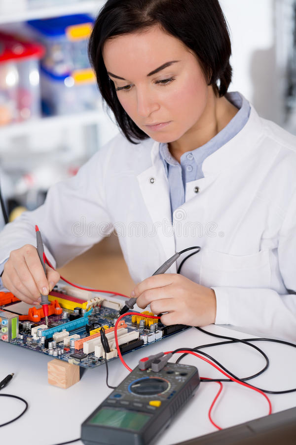 Girl student studying electronic device with a microprocessor. Girl student studying electronic device with microprocessor stock images