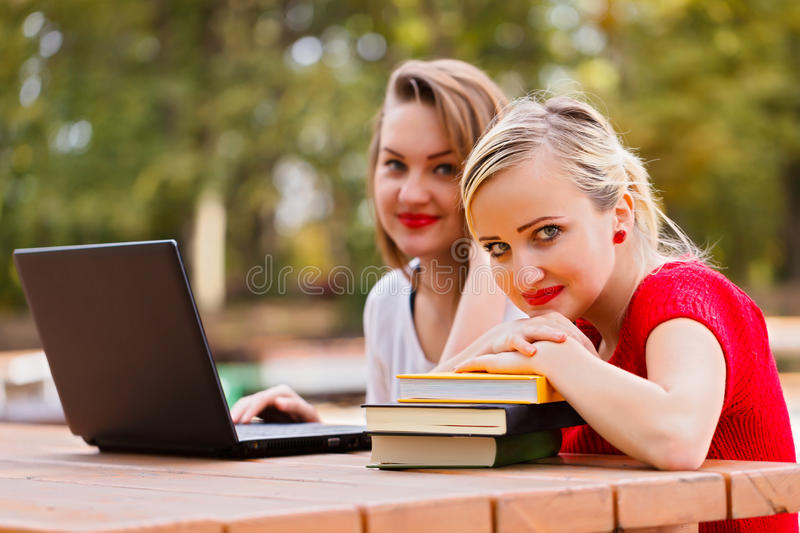 Girl Students. Beautiful girl students with laptops outdoors in the university campus stock image