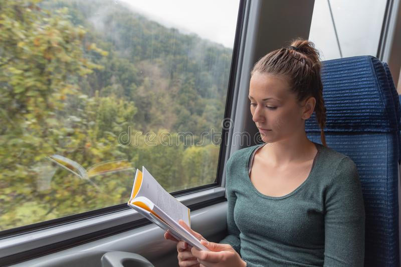 Young cute woman reading a book while travelling by train stock photo