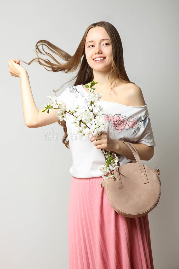 Girl in stylish spring clothes with fashionable round handbag. Beautiful smiling girl in stylish spring clothes with fashionable round handbag and blooming sprig royalty free stock photos