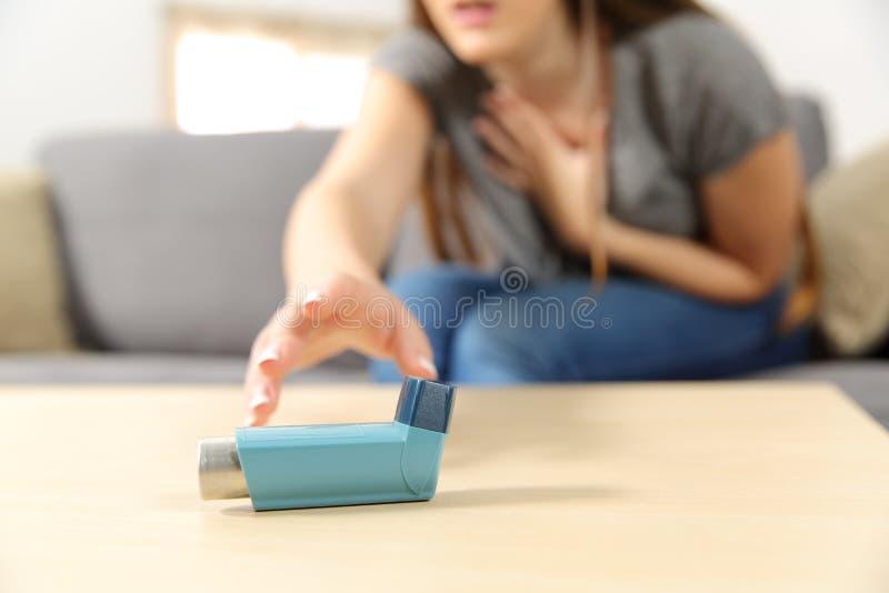 Girl suffering asthma attack reaching inhaler stock photos