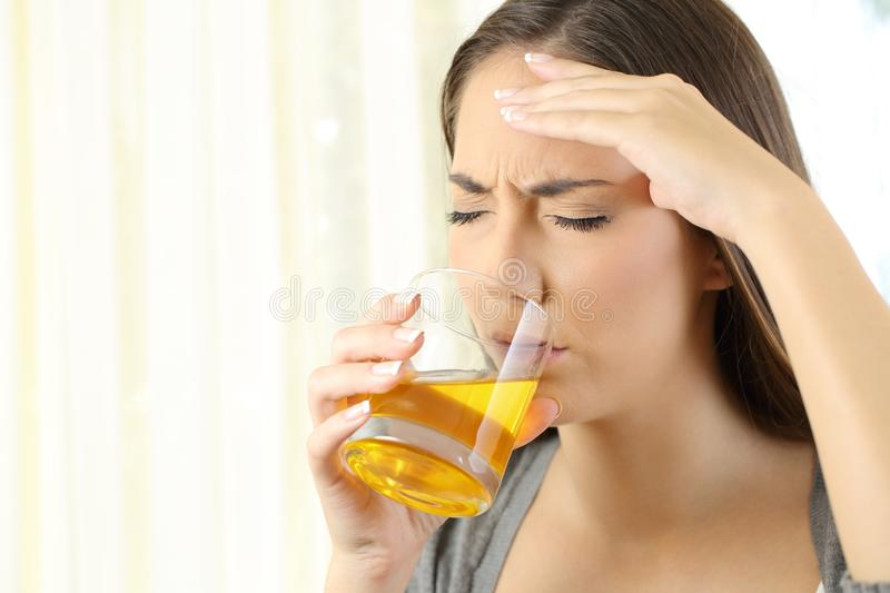 Girl suffering headache drinking a medicine royalty free stock photography