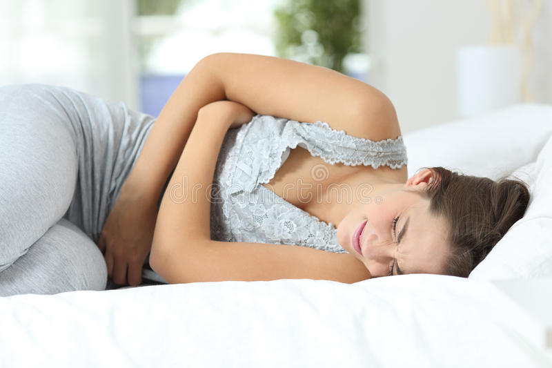 Girl suffering menstrual pains on the bed. Girl suffering menstrual pains lying on the bed at home stock photos