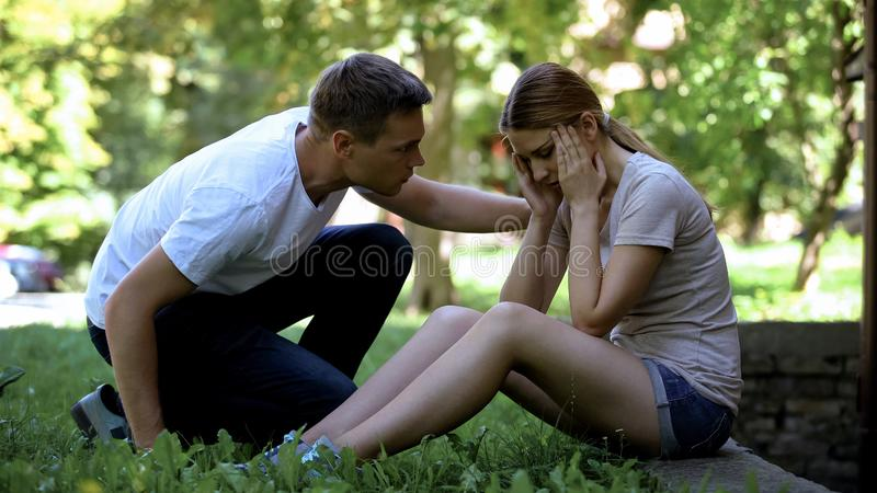 Girl suffering from migraine, sitting in park, man calling ambulance, first aid. Girl suffering from migraine, sitting in park, men calling ambulance, first aid stock images