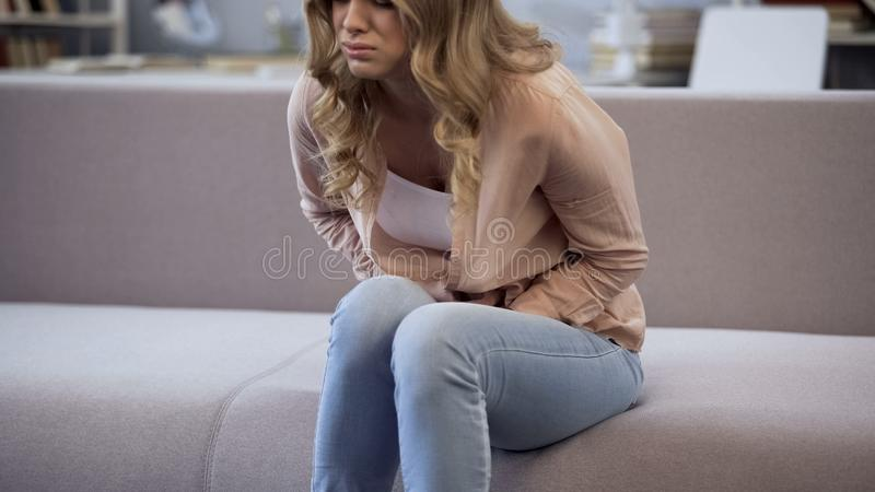 Girl suffering from stomach pain, premenstrual syndrome spasms, women health stock images