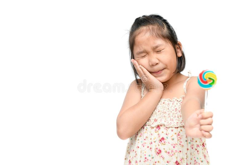 Girl suffering from toothache and holding candy. Little Asian girl suffering from toothache and holding candy in hand isolated on white background, Dental royalty free stock photo