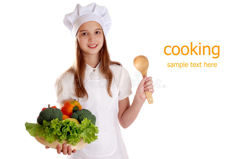 The girl in a suit of the cook with a basket of vegetables and fruits on isolated background.  royalty free stock photo