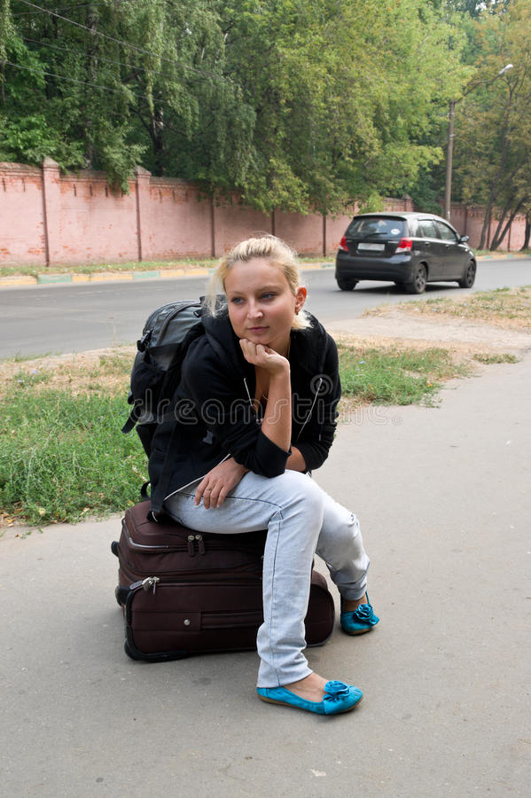 Girl with a suitcase. Girl sitting on a suitcase and waiting for a lift royalty free stock images