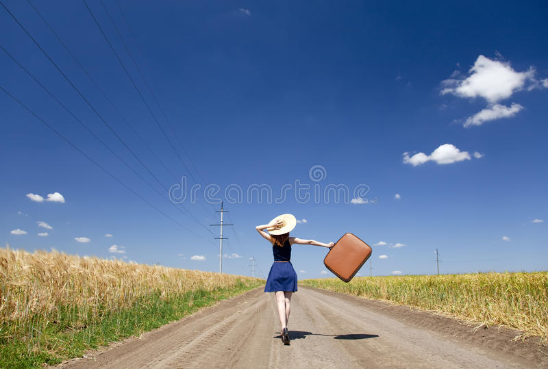 Girl with suitcase at country road. stock images