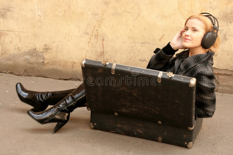 Girl in suitcase listening to music royalty free stock images