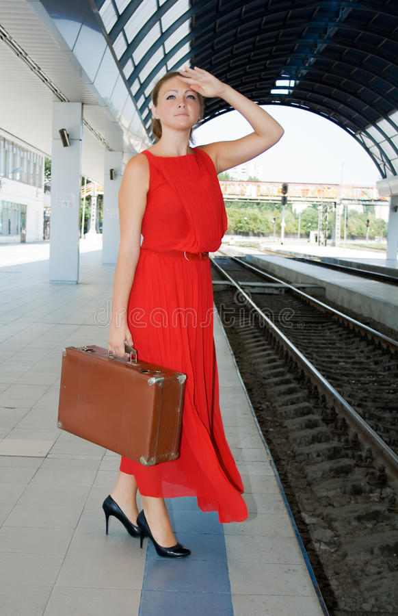 Girl with a suitcase at the railway station royalty free stock photo