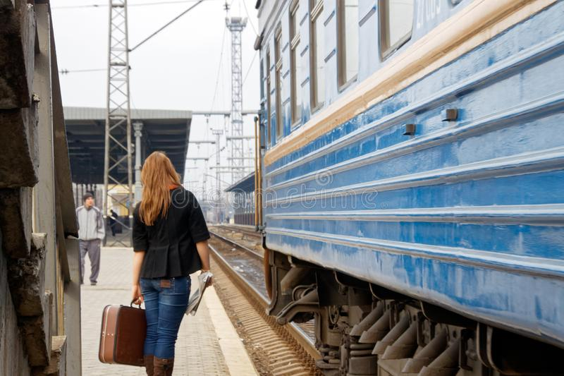 A girl with a suitcase is standing near a passenger train. Kharkiv, Ukraine - March 25, 2012: A beautiful girl with a brown vintage travel suitcase is standing stock image