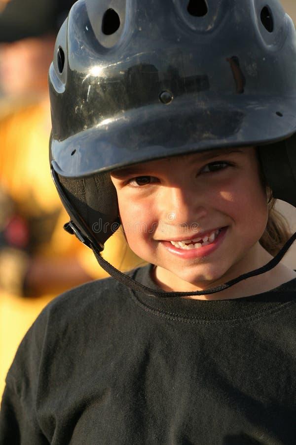Girl Of Summer. Young smiling Hispanic/American girl with baseball helmet stock photo