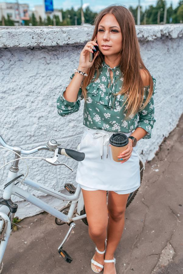 Girl in the summer in city, calls on the phone, with a bicycle, in her hand a cup of coffee tea. Long hair tanned skin royalty free stock image
