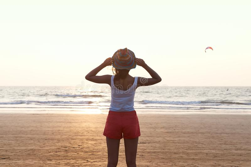 A girl in summer clothes shorts and a hat looking at the sun and the sea, in front of her back to the camera. On the background of the Sunny sunset sky and the stock photos