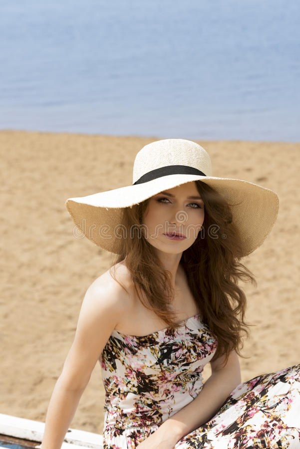Girl in summer dress on the beach. Romantic portrait of young woaman , sitting on the beach , wearing a summer hat and floral dress , sand on background royalty free stock images