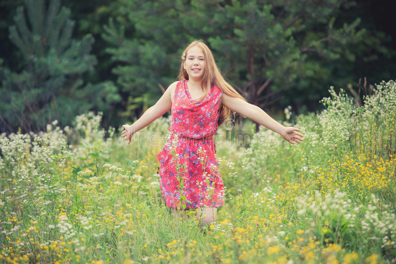 Girl in summer field. Young girl teen with long brown hair enjoying the atmosphere of summer field in warm day stock image