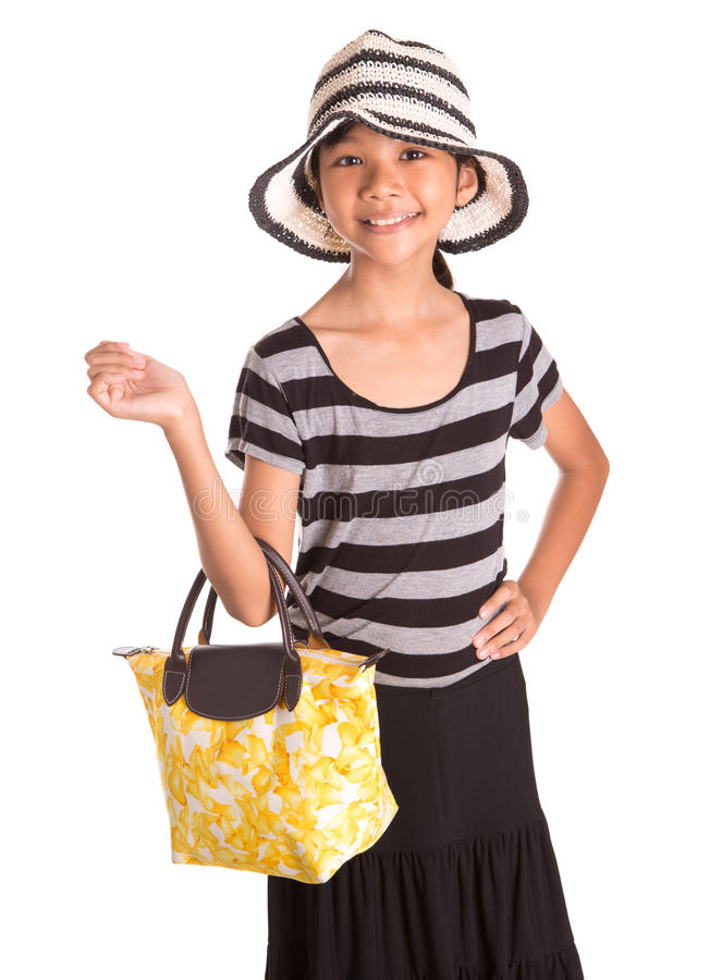 Girl With Summer Hat, And Handbag III. Young Asian Malay girl with a large summer hat and a yellow handbag over white background royalty free stock photo