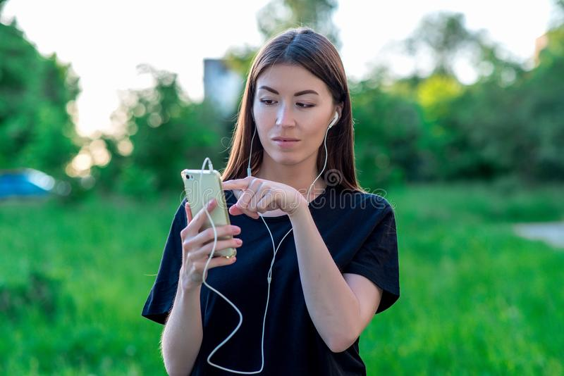 Girl in summer in a park nature. Holds a smartphone with headphones. Finger of the hand dials a message. Opens a new. Girl in summer in a park in nature. Holds a royalty free stock photos