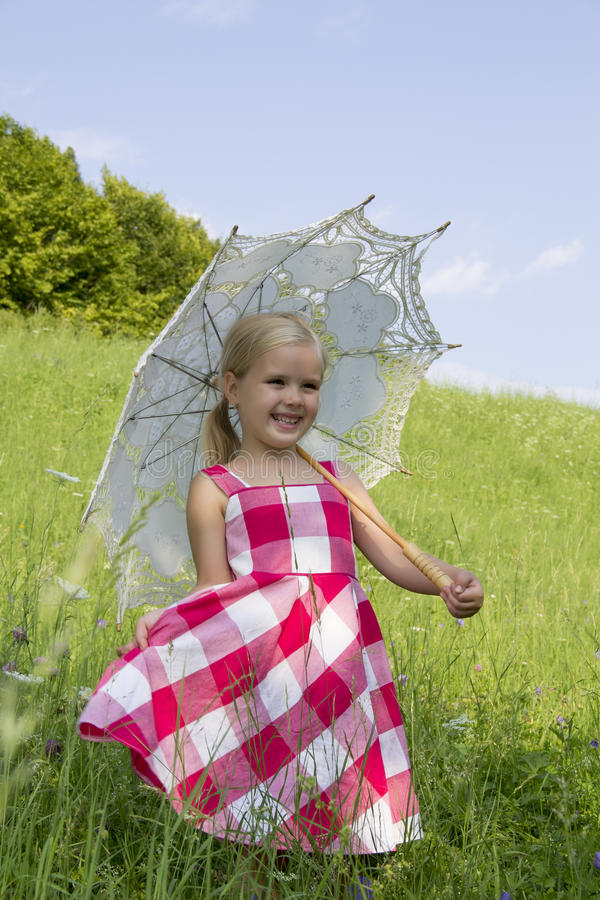 Girl with a summer umbrella. A girl with a summer umbrella stands on a meadow royalty free stock photo