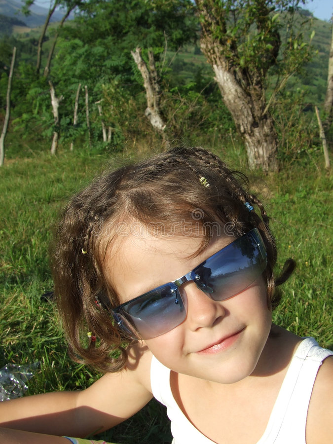 Girl with sun glasses. Beautiful girl with blue transparent sun glasses in the nature. Beautiful smile royalty free stock photos