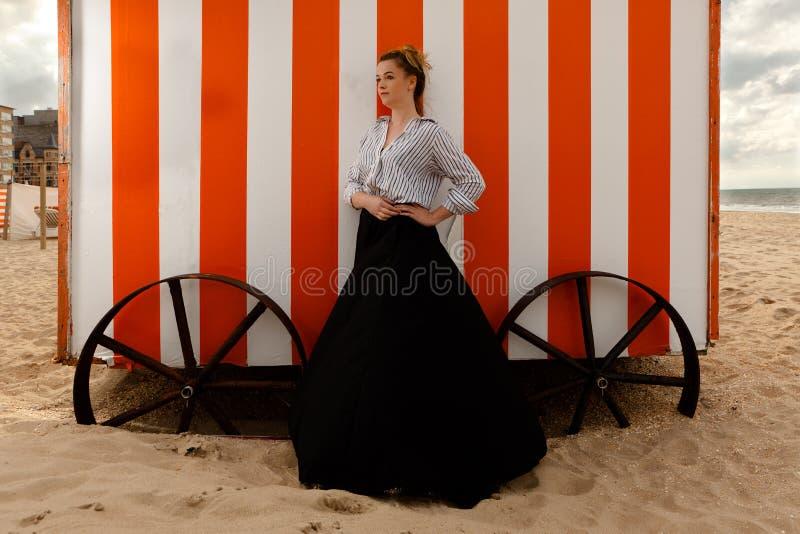 Girl sun sand hut, De Panne, Belgium royalty free stock image