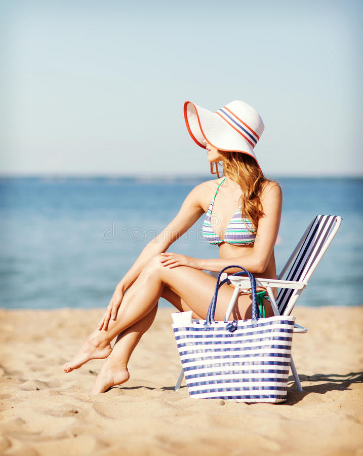 Girl sunbathing on the beach chair stock photography