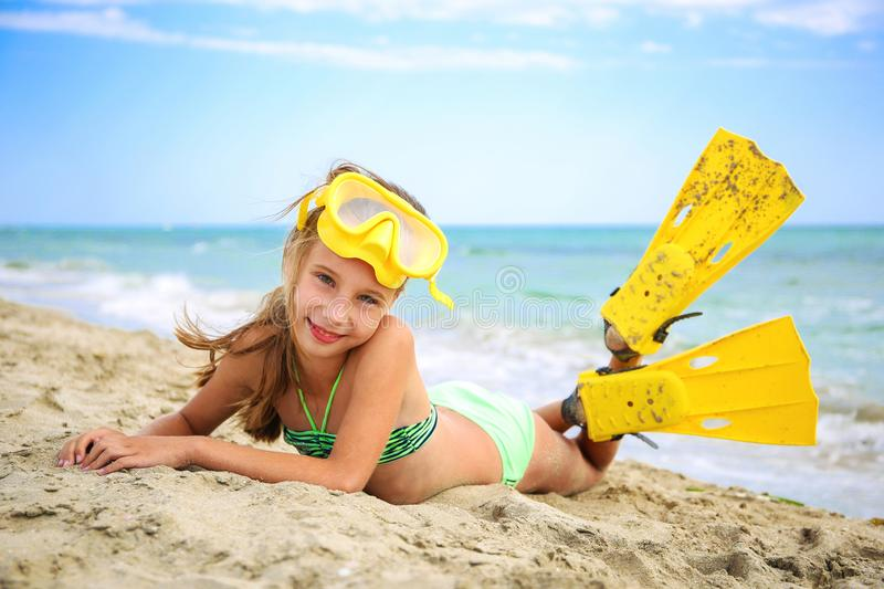 Girl sunbathing in mask and fins for scuba diving. Girl sunbathing on beach in mask and fins for scuba diving royalty free stock image