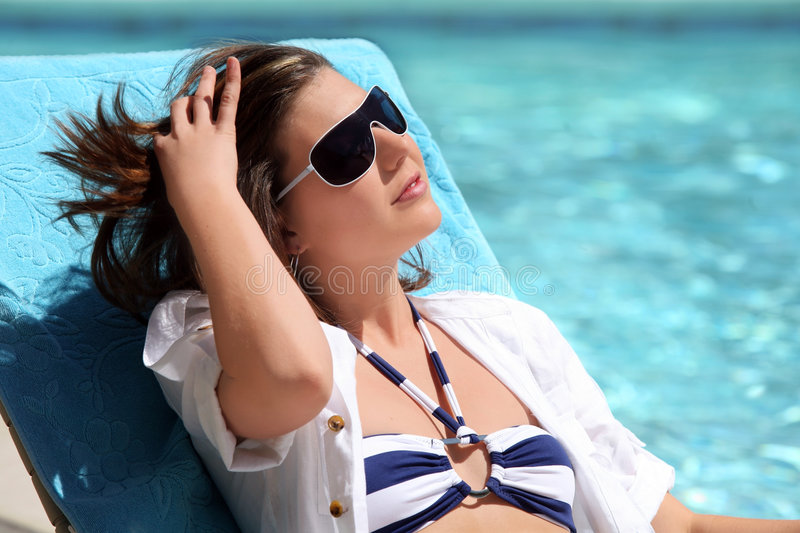 Girl Sunbathing By The Pool Stock Images