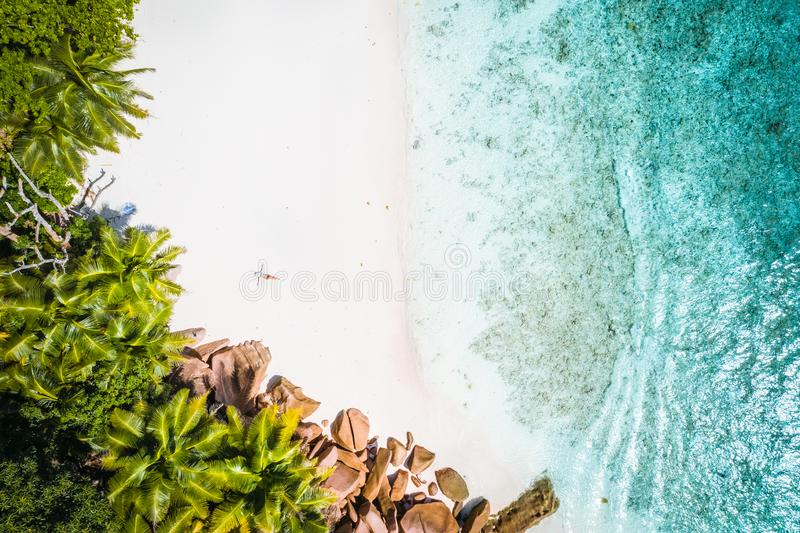 Girl sunbathing on tropical sandy beach surrounded by brown rocks, coconut palm trees and turquoise azure ocean lagoon stock photos