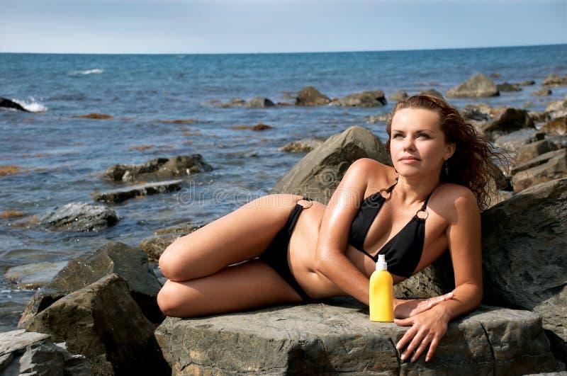 Download Girl of sunburn on stones stock image. Image of cream - 7548399