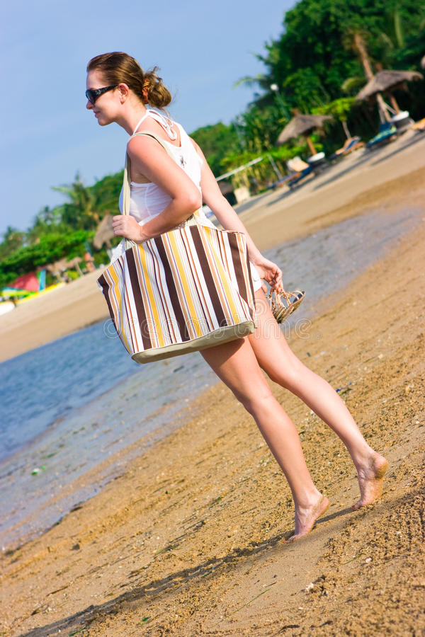 Girl With Sunglasses And Bag On The Beach Royalty Free Stock Photography