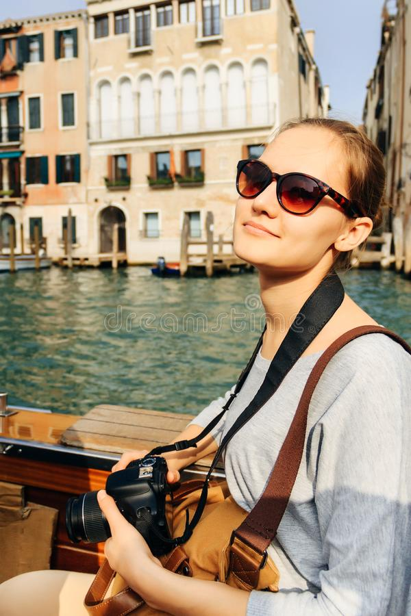 Girl in sunglasses Venice floats, vertically. Girl in sunglasses with camera floating in Venice, vertically royalty free stock images