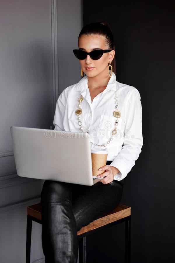 Girl in sunglasses, sitting on chair and working on laptop and holding a cup a coffe over black and grey background. stock photos