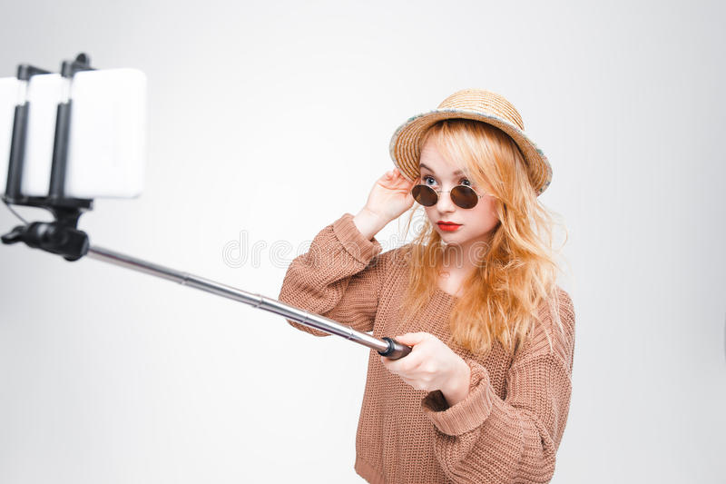 Girl in sunglasses takes photo with selfie stick. Young girl in sunglasses and straw hat takes photo with selfie stick. Fashionable hipster girl having fun stock photography
