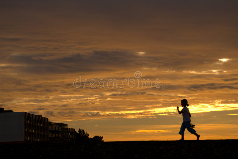 Girl at sunset. Small girl walking in a sunset boulevard in the beach of arcachon royalty free stock image