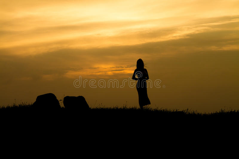 Girl on Sunset rock - Silhouette stock photography