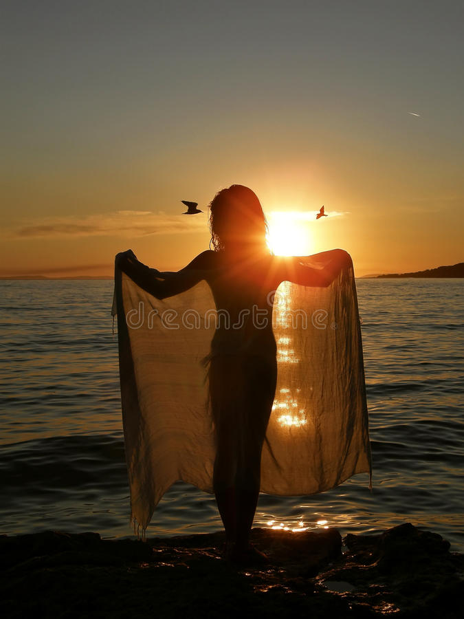 Girl In Sunset With Scarf And Birds Stock Photo