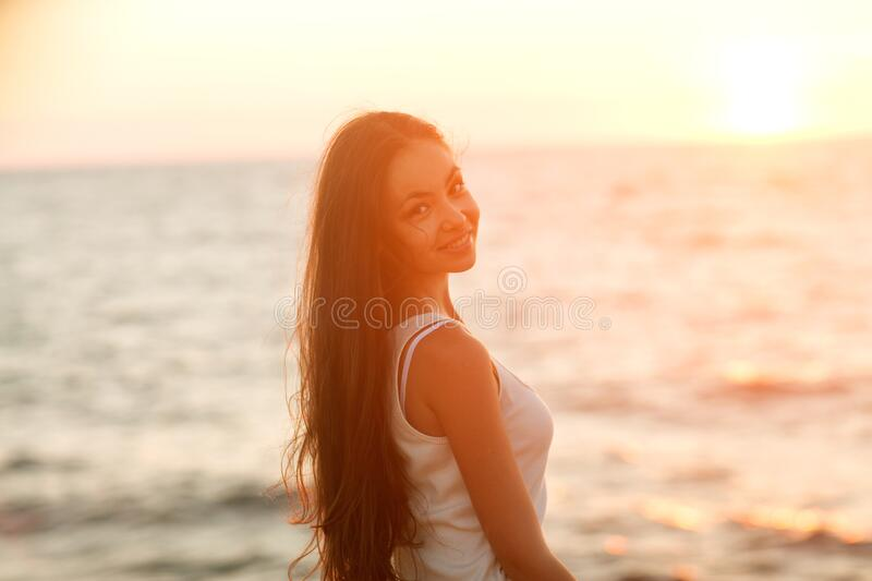 Girl at sunset by the sea smiling stock photography